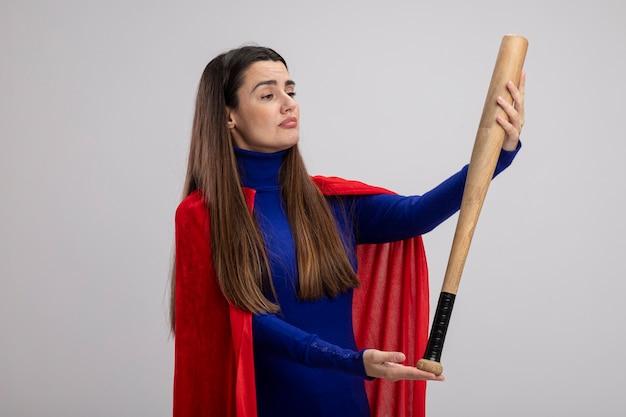 Beeindrucktes junges superheldenmädchen, das baseballschläger lokalisiert auf weiß hält und betrachtet