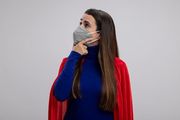 Beeindrucktes junges superheldenmädchen, das seite betrachtet, die medizinische maske trägt, die hand unter kinn lokalisiert auf weiß setzt