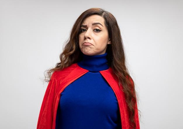 Beeindrucktes kaukasisches superheldenmädchen mit rotem umhang betrachtet kamera auf weiß