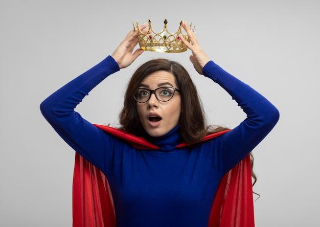 Beeindrucktes kaukasisches superheldenmädchen mit rotem umhang in optischer brille hält krone über kopf auf weiß