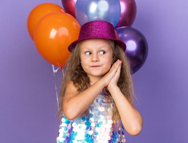 Beeindrucktes kleines blondes mädchen mit violettem partyhut, das die hände zusammenhält und die seite mit heliumballons isoliert auf lila wand mit kopienraum betrachtet