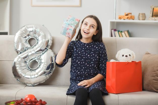 Beeindrucktes kleines mädchen am tag der glücklichen frau, das geschenk auf dem sofa im wohnzimmer hält