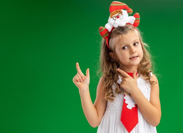 Beeindrucktes kleines mädchen, das weihnachtshaarbügel mit krawattenpunkten hinten lokalisiert auf grünem hintergrund trägt