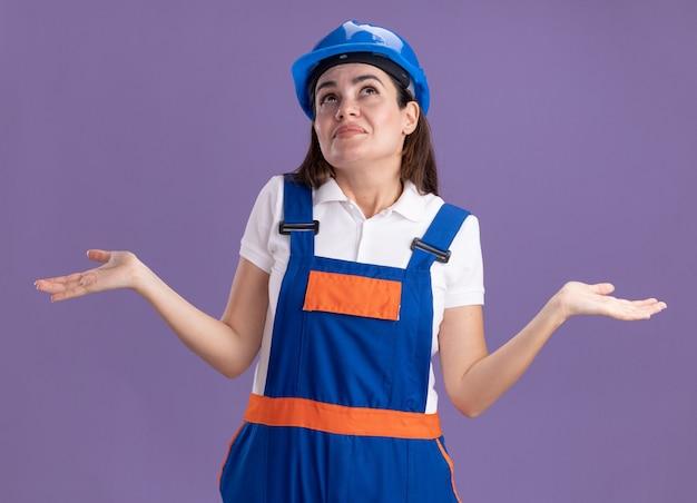 Beeindrucktes nachschlagen der jungen baumeisterin in uniform, die hände auf lila wand isoliert spreizt
