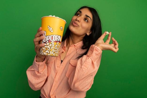 Beeindrucktes nachschlagen des jungen schönen mädchens, das rosa t-shirt hält, das eimer popcorn und popcornfrieden hält, lokalisiert auf grüner wand