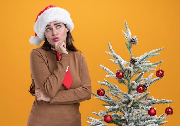 Beeindrucktes nachschlagen des jungen schönen mädchens, das weihnachtshut mit krawatte steht, die nahe weihnachtsbaum steht, packte kinn lokalisiert auf orangefarbenem hintergrund
