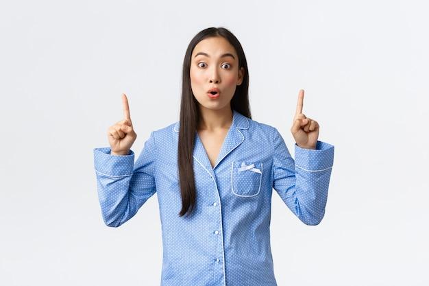 Beeindrucktes und aufgeregtes, attraktives asiatisches mädchen in blauen pyjamas, das über promo spricht, die kamera überrascht, als sie mit den fingern nach oben zeigt und top-werbung zeigt, steht auf weißem hintergrund.