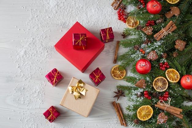 Beeren, äpfel, orangenscheiben, schnee, zimt und geschenke in verschiedenen formen und farben