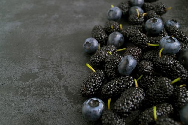 Beeren auf schwarzem hintergrund, blaubeere und maulbeere.
