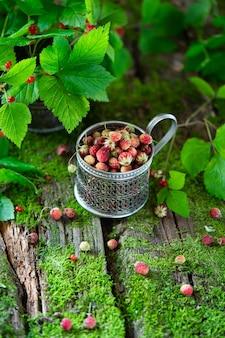 Beeren aus dem wald. knochen- und erdbeerbeeren auf altem hölzernem hintergrund mit moos