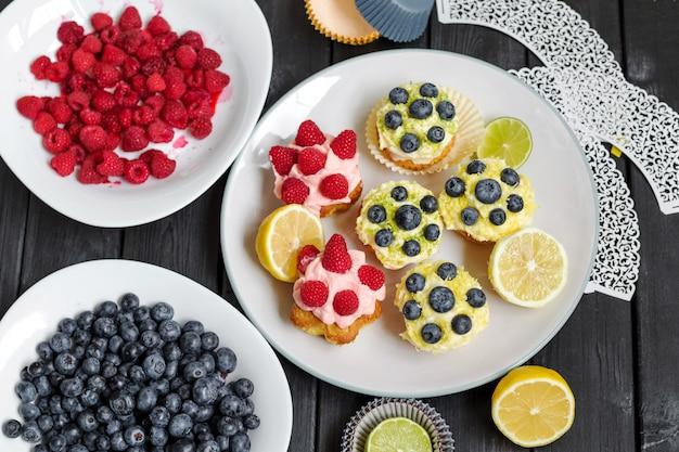 Beeren-cupcakes mit buttercreme auf schwarzem holztisch.