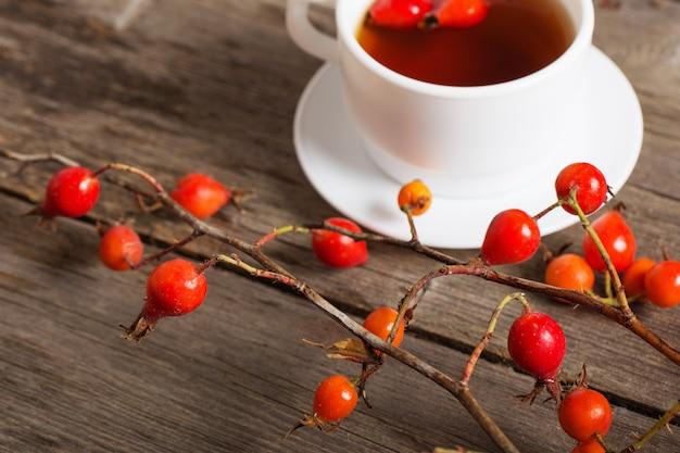 Beeren der dogrose und des tees auf hölzernem hintergrund