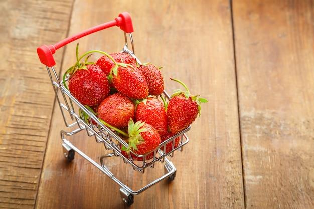 Beeren einer roten erdbeere in einem einkaufswagen auf einem hölzernen hintergrund. horizontales foto