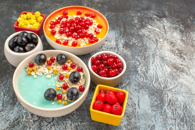 Beeren-haferflocken der seiten-nahaufnahmeansicht mit granatapfelkernen-trauben-kirschen-bonbons mit roten johannisbeeren