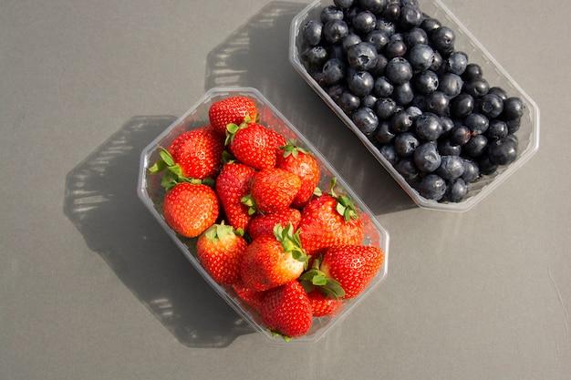 Beeren in einem plastikbehälter. frische erdbeere und blaubeere im plastikkasten