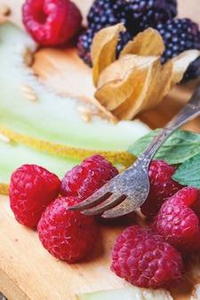Beeren, minze und melone auf holzbrett