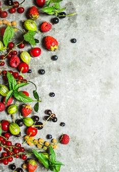 Beeren mit minzblättern auf steinhintergrund.