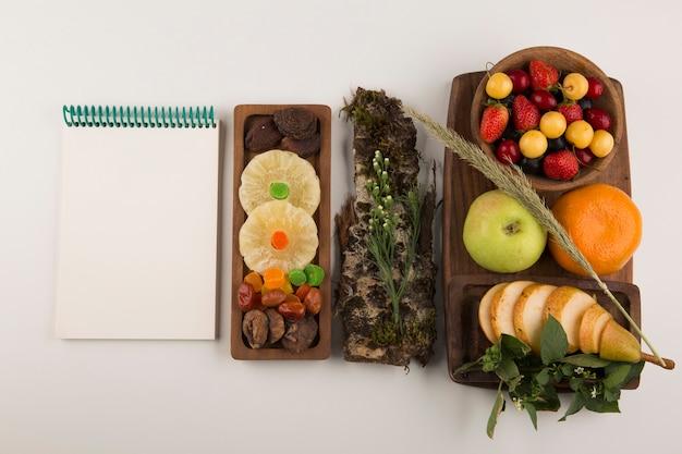 Beeren, obstmischung und kräuter auf einer holzplatte mit einem notizbuch beiseite