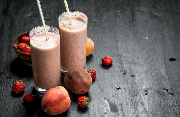 Beeren-smoothie mit früchten. auf schwarzem hintergrund.