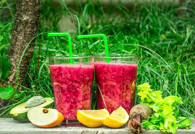 Beeren-smoothie mit gemüse und obst. auf dem sommerhintergrund.