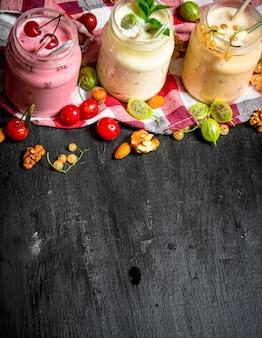 Beeren-smoothie mit minze und nüssen. auf der schwarzen tafel.