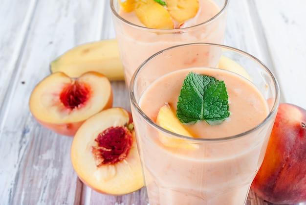 Beeren-smoothies von aprikose, pfirsich und banane in gläsern und zutaten auf einem holztisch