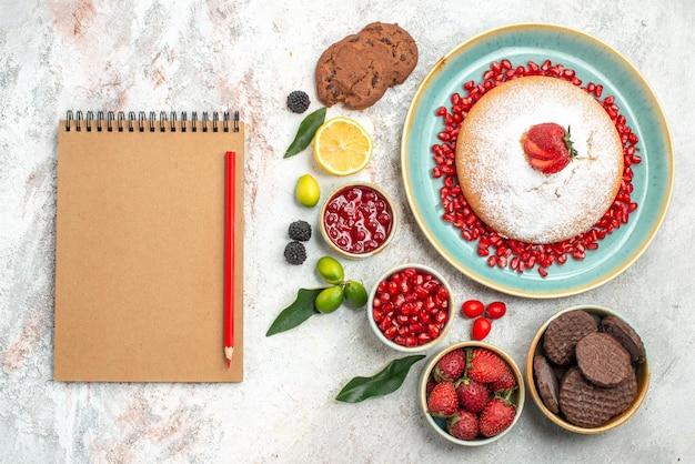 Beeren und kekse der appetitliche kuchen mit beerenmarmelade kekse notizbuch bleistift