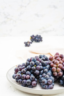 Beeren von reifen blauen trauben auf einer platte auf einer tabelle