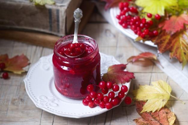Beeren von rotem viburnum mit zucker und honig in einem glasgefäß mit büchern, beeren und blättern.