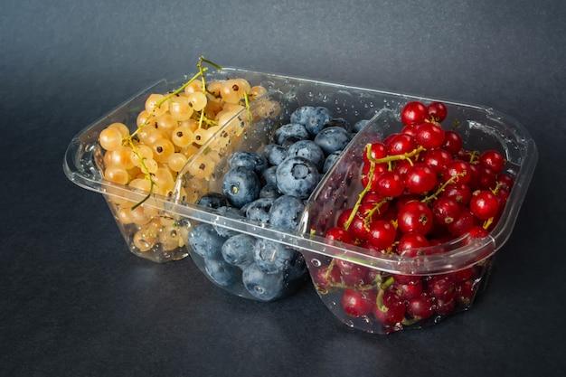 Beeren von roten und weißen johannisbeeren und blaubeeren in plastikverpackung.