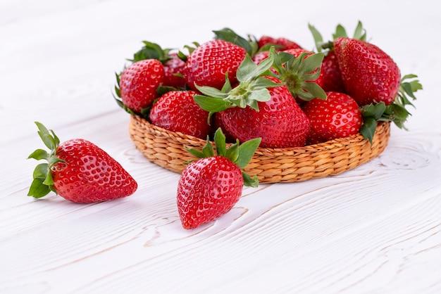Beeren von saftigen erdbeeren in einer weidenschale auf einem weißen schäbigen holztisch im rustikalen stil.