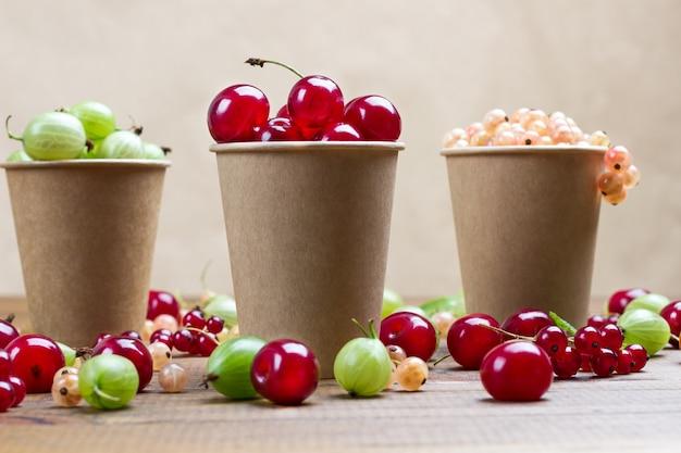 Beeren von weißen johannisbeeren, grüne stachelbeeren, kirschen in papierkappen. beeren auf dem tisch. hölzerner hintergrund.