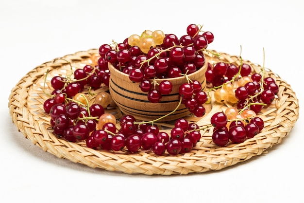 Beeren von weißen und roten johannisbeeren auf korbteller. weißer hintergrund. ansicht von oben