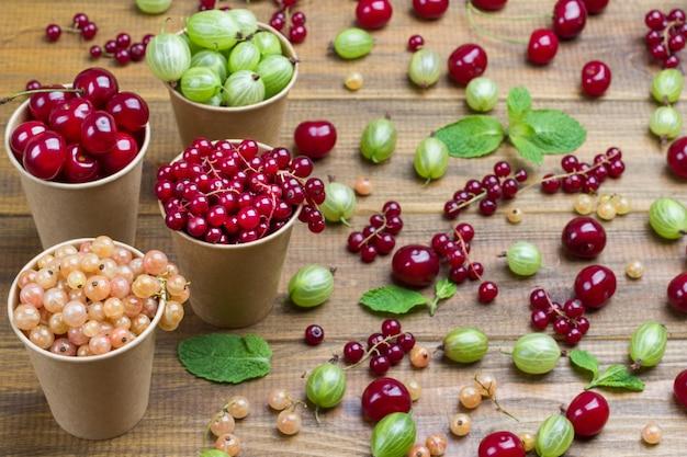 Beeren von weißen und roten johannisbeeren, grüne stachelbeeren, kirschen in papierkappen. beeren und minze auf dem tisch. hölzerner hintergrund. ansicht von oben