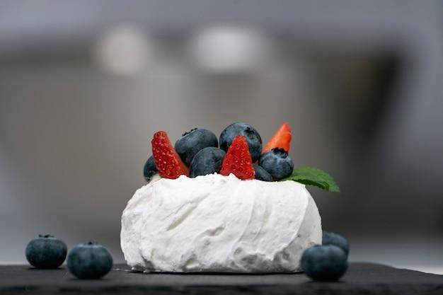 Beerendessert, nahaufnahme. baiser mit frischen erdbeeren und blaubeeren. kuchen anna pavlova.