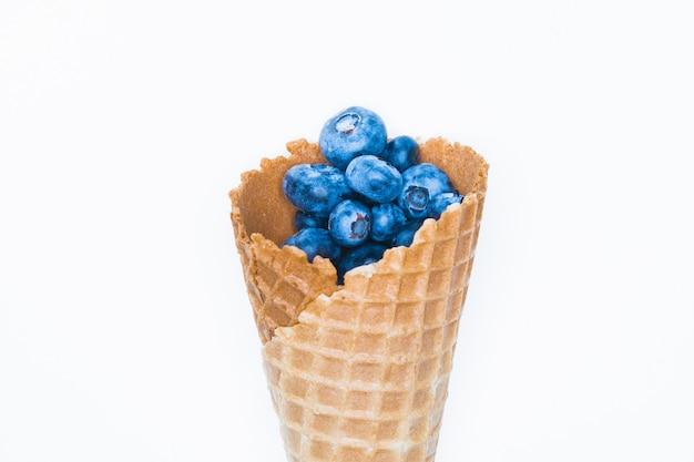 Beereneis. blaubeere in einem horn. auf einem hintergrund für eine inschrift. hand und eis. draufsicht vitaminkonzept. platz für eine inschrift. beerenliebeskonzept.