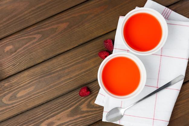 Beerenfruchtgelee mit frischen beeren auf holzhintergrund, lebensmittelkonzept. zwei teller mit süßem dessert