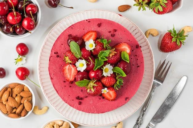 Beerenkäsekuchen mit frischen erdbeeren, kirschen und blumen auf weiß mit messer und gabel. draufsicht