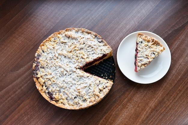 Beerenkuchen schneiden. scheibe hausgemachte sauerkirschpastete auf teller und ganze torte in scheiben geschnitten in auflaufform auf serviette auf holztisch, klassisches rezept, ansicht von oben