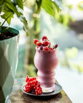 Beerenmilchshake garniert mit himbeererdbeeren und preiselbeeren in bambusspießen
