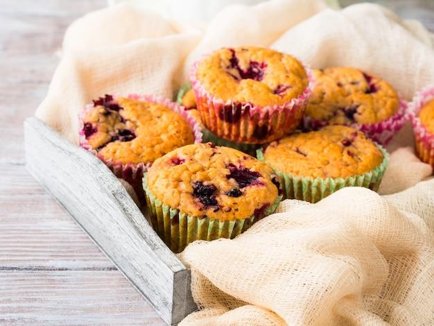 Beerenmuffins im hölzernen behälterserviettenfrühstück