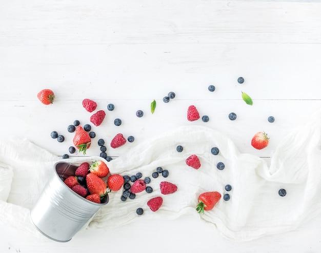 Beerenrahmen mit kopienraum auf recht. blecheimer, erdbeeren, himbeeren, blaubeeren und tadellose blätter, weißer hölzerner hintergrund, draufsicht