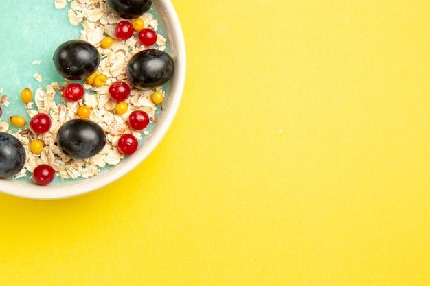 Beerenschale der oberen nahaufnahmeansicht des appetitlichen gerichts der roten johannisbeeren der schwarzen trauben auf dem gelben tisch