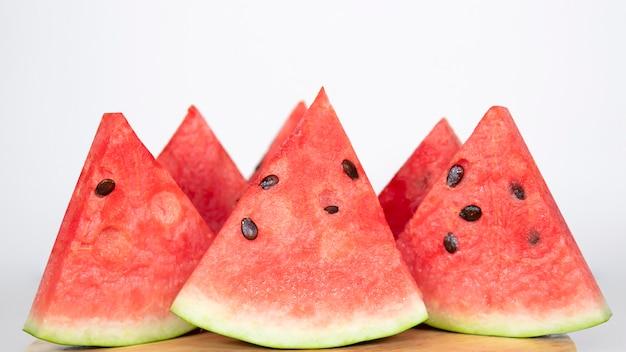 Beerenwassermelone im wasser spritzt auf ein holztablett. reflexion auf dem tisch.