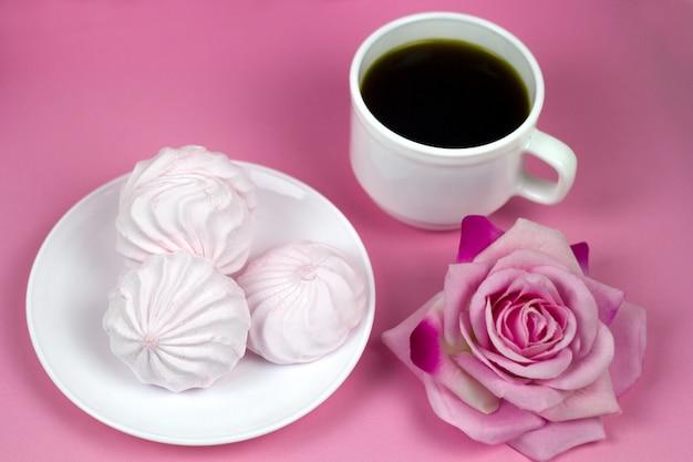 Beerenzefir und kaffeetasse auf einem rosa hintergrund