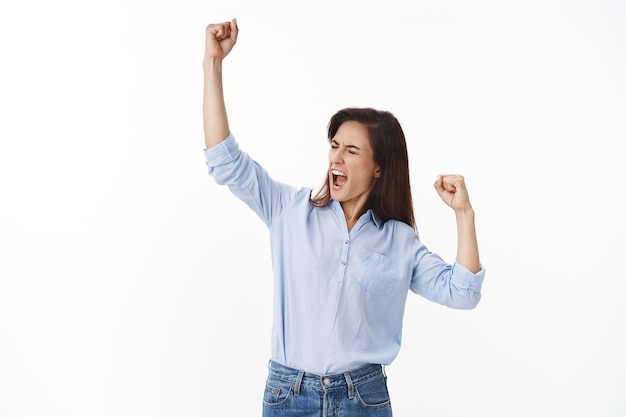 Befähigte triumphierende, fröhliche frau mittleren alters, die erfolg feiert, faustpumpen-sieggeste, geschlossene augen schreien oh ja ja, siegertanz, selbstbewusst motiviert stehen, ausgezeichnete nachrichten erhalten