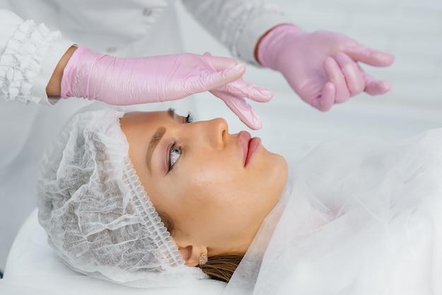 Befeuchten der lippen während eines kosmetischen eingriffs für eine junge frau