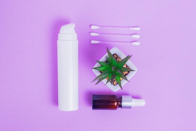 Befeuchtende gesichtscreme mit kollagen und mucin einer schnecke für die haut des gesichts gegen falten und akne in einer weißen packung mit pumpe und gesichtsserum in einer glasflasche mit make-up-sticks