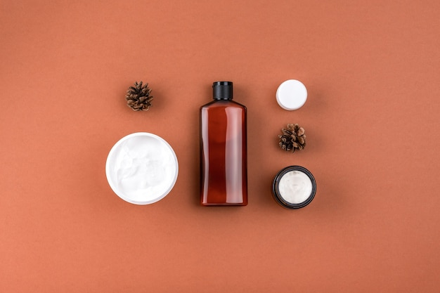 Befeuchtende gesichtsmaskencreme im offenen glas, modellflasche lotion. hautpflegeprodukte mit natürlichen inhaltsstoffen auf brauner oberfläche.