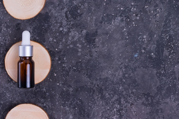 Befeuchtendes serum mit kollagen und mucin einer schnecke für die gesichtshaut gegen falten und akne in einer glasflasche auf einem holzständer auf einem grauen tisch